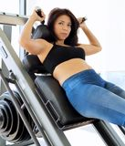 Woman wearing sports bra uses squat machine Royalty Free Stock Photo