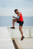 Fit athlete doing toe taps workout. Athlete doing toe taps hiit exercise for warming up before running. Black young runner training towards the sea Royalty Free Stock Photography