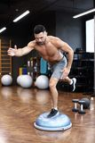 Fit athlete performing exercise on gymnastic hemisphere bosu ball in gym.  stock images