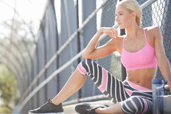 Fit athlete sits along a pathway. Attractive blonde athlete resting outdoors in sports wear Royalty Free Stock Photo