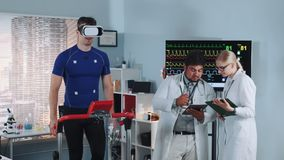 Fit athlete in VR glasses walking on treadmill in sports lab. While two doctors discussing his EKG data stock video footage
