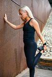 Fit athlete woman stretching after workout against metal wall in the city stock image
