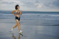 Fit and athletic Asian Chinese sporty woman running on beautiful beach doing jogging workout on sunset in fitness healthy lifestyl stock photos