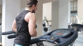 Fit athletic man is starting to run on the treadmill in the sport gym stock footage