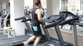 Fit athletic man is starting to run on the treadmill in the sport gym.  stock video