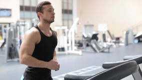 Fit athletic man is starting to run on the treadmill in the sport gym stock video