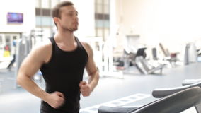 Fit athletic man is starting to run on the treadmill in the sport gym stock video footage