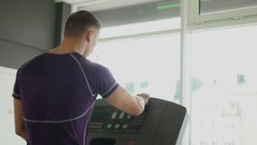 Fit athletic man is starting to run on the treadmill in the sport gym.  stock video footage