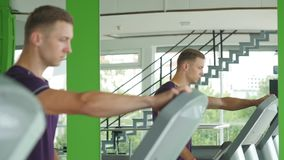Fit athletic man is starting to run on the treadmill in the sport gym Stock Images