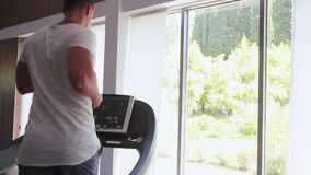 Fit athletic man is starting to run on the treadmill in the sport gym.  stock footage