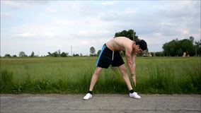 Fit, athletic shirtless young man outdoor doing stretching exercises stock video