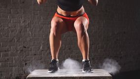 Fit athletic woman does box jumps in the deserted factory gym. Intense exercise is part of her daily cross fitness