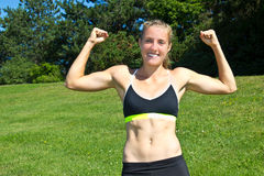 Fit, athletic woman flexing her muscles Royalty Free Stock Image
