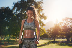 Fit and athletic woman in park with a jump rope. Fit and athletic young woman standing in a park with a jump rope. Young woman aerobics instructor with jumprope Stock Photos