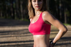 Fit athletic woman standing in a forest, sweating and taking a break from intense workout. Stock Images