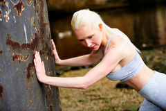 Fit athletic woman stretching against a wall Royalty Free Stock Images