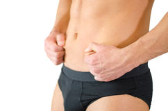 Fit young man pinching his belly skin Royalty Free Stock Photos