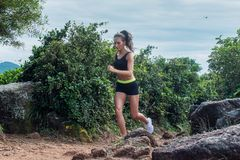 Fit athletic young woman running on dirty rocky path in mountains in summer. Fit athletic young woman running on dirty rocky path in mountains in summer Royalty Free Stock Images