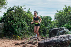 Fit athletic young woman running on dirty rocky path in mountains in summer. Fit athletic young woman running on dirty rocky path in mountains in summer Royalty Free Stock Photography