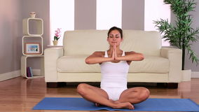 Fit attractive brunette doing yoga exercise in living room stock video