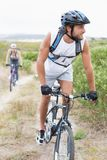 Fit attractive couple cycling on mountain trail Stock Images
