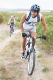 Fit attractive couple cycling on mountain trail Royalty Free Stock Image