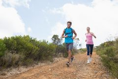 Fit attractive couple jogging down mountain trail Stock Photos