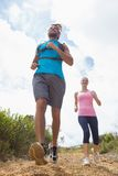 Fit attractive couple jogging down mountain trail Stock Images