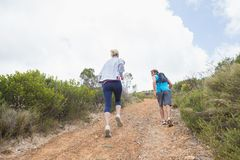 Fit attractive couple jogging up mountain trail Royalty Free Stock Images