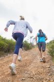 Fit attractive couple jogging up mountain trail Royalty Free Stock Image