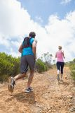 Fit attractive couple jogging up mountain trail Royalty Free Stock Photography