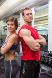 Fit attractive couple smiling at camera with arms crossed stock photography