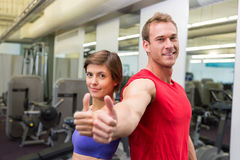 Fit attractive couple smiling at camera showing thumbs up Royalty Free Stock Photography