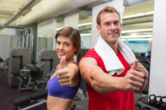 Fit attractive couple smiling at camera showing thumbs up Royalty Free Stock Image