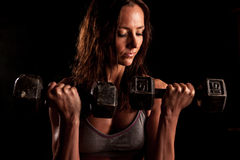 A fit attractive woman lifting weights Stock Images
