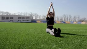 Fit attractive young active woman does yoga stretch pose on huge stadium green grass meditating calmly on warm sunny day stock footage