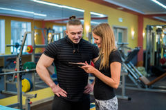 Fit attractive young couple at a gym looking at a tablet-pc as they monitor their progress and fitness Royalty Free Stock Images