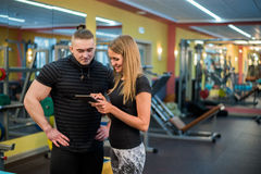 Fit attractive young couple at a gym looking at a tablet-pc as they monitor their progress and fitness Stock Images