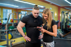 Fit attractive young couple at a gym looking at a tablet-pc as they monitor their progress and fitness Stock Photography