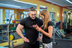 Fit attractive young couple at a gym looking at a tablet-pc as they monitor their progress and fitness Royalty Free Stock Photos