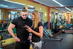 Fit attractive young couple at a gym looking at a tablet-pc as they monitor their progress and fitness Stock Photos
