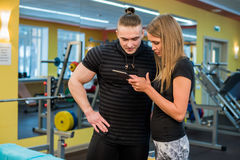 Fit attractive young couple at a gym looking at a tablet-pc as they monitor their progress and fitness Royalty Free Stock Photo