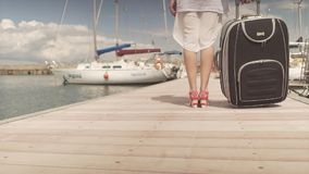 Fit attractive young woman in high heels turn back walking on wooden bridge carrying heavy luggage in yacht boat harbor. Young woman in high heels walking on stock video footage