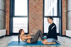 Fit awesome girl doing exercises with a coach. In the loft room,sport activity. body and health care. full length photo stock photo