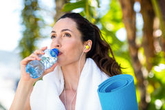 Fit beautiful brunette drinking water while listening music Royalty Free Stock Image