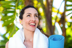 Fit beautiful brunette listening music and holding exercise mat Royalty Free Stock Photos