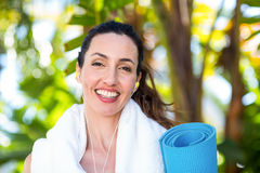 Fit beautiful brunette listening music and holding exercise mat Stock Image