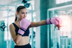 Fit beautiful woman boxer hitting a huge punching bag exercise class in a gym. Boxer woman making direct hit dynamic movement. royalty free stock image