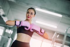 Fit beautiful woman boxer hitting a huge punching bag exercise class in a gym. Boxer woman making direct hit dynamic movement. Healthy, sports, lifestyle stock photo