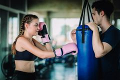 Fit beautiful woman boxer hitting a huge punching bag exercise class in a gym. Boxer woman making direct hit dynamic movement. Fit beautiful women boxer hitting stock photography